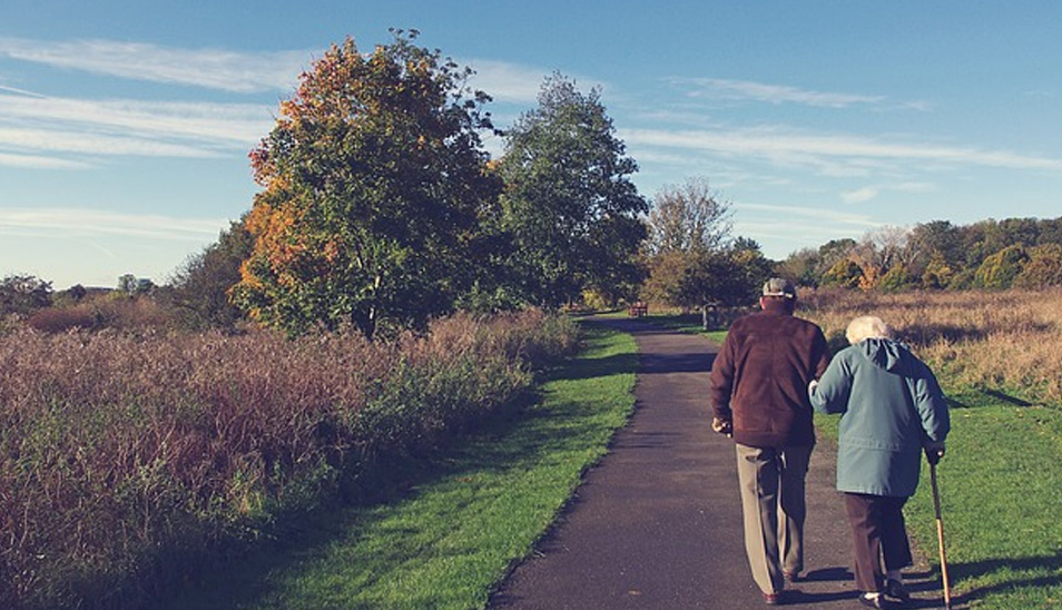 elderly couple walking up a path on cold autumn day