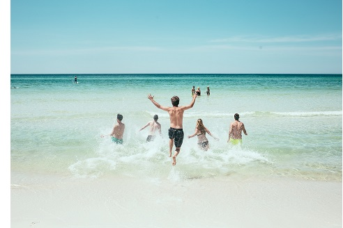 friends running on white sand beach into ocean with arms raised