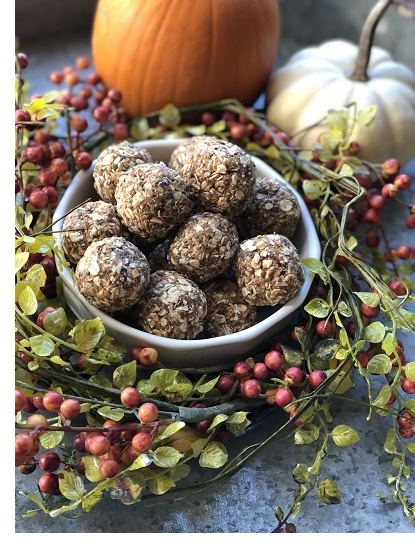 pumpkin spiced protein balls covered in oats and whey sitting in bowl surrounded by leaves, berries, and pumpkins
